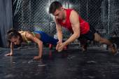 Sportsmen. fit male trainer man and woman doing clapping push-ups explosive strength training concept crossfit fitness workout strenght power — Stock Photo