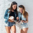 Two beautiful girls friends reading the magazine wearing sunglasses and denim jeans jackets shorts urban street casual style — Stock Photo #70567983