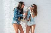 Two pretty girls wearing sunglasses in summer jeanswear street urban casual style talking, laughing having fun on the background of brick wall. — Stock Photo