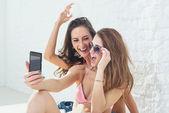 Koleżanki, śmiejąc się, że zabawa przy selfie razem na sobie bikini biustonosz kąpielowy lato słoneczny dzień ulica miejskiego stylu casual — Zdjęcie stockowe