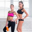 Two young sportive active fit and slim beautiful woman posing in sportswear indoors with the window — Stok fotoğraf #70687129