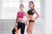 Two young sportive active fit and slim beautiful woman posing in sportswear indoors with the window — Stock Photo