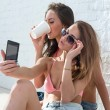 Female friends drinking coffee taking self-portrait picture photos with mobile smart phone or pocket camera on vacation wearing bikini bra swimsuit summer sunny day street urban casual style — Stock Photo #70906039