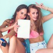 Two attractive beautiful young women in summer outfit street urban casual style having fun  taking self-portrait picture photos with the tablet sitting on ground red bikini bra swimsuit sunny day — Stock Photo #70906235