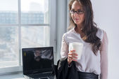 Young woman in glasses with the cup of coffee or tea her hands standing near window. — Stock Photo
