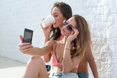 Female friends drinking coffee taking self-portrait picture photos with mobile smart phone or pocket camera on vacation wearing bikini bra swimsuit summer sunny day street urban casual style — Stock Photo