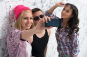 Two women and man friends taking selfie together wearing summer clothes  jeans shorts jeanswear street urban casual style having fun. — Stock Photo