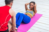 Athletic sporty couple friends. Woman doing crunches abdominal exercises on floor in gym with a help of guy concept training exercising workout fitness aerobic — Stock Photo