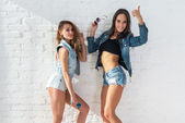 Two pretty happy female friends in summer jeanswear street urban casual style talking, laughing having fun on the background of brick wall. — Stockfoto