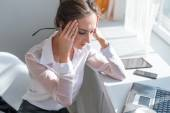 Portrait of tired young business woman suffering from headache in front laptop at office desk — Stock Photo