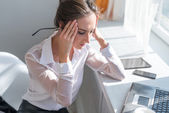 Portrait of tired young business woman suffering from headache in front laptop at office desk — Fotografia Stock