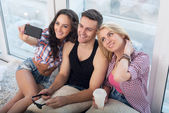 Happy friends two women and man taking selfie with camera or smartphone together wearing summer clothes  jeans shorts jeanswear street urban casual style having fun. — Стоковое фото