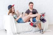 Young friends funny guys active people have fun together sitting on sofa send message chatting using app gaming with their smartphones at home concept social media — Stock fotografie