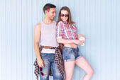 Happy couple friends wearing sunglasses in summer jeanswear street urban casual style talking having fun standing near wall — Stock Photo
