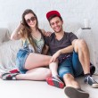 Friends girl and guy sitting on floor at home in summer jeanswear street urban casual style talking, having fun — Stock Photo #72921929