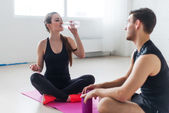 Sport connecting people friends relaxing after workout girl drinking water and man Side view of young couple in sports clothing sitting talking conversing. — Foto de Stock