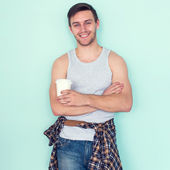 Portrait young man arms crossed holding paper cup of coffee city street casual urban style looking at camera standing near wall. — Stock Photo