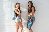 Two pretty happy female friends in summer jeanswear street urban casual style talking, laughing having fun on the background of brick wall. — Stock Photo