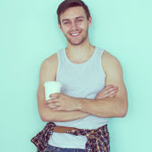 Portrait young man holding paper cup of coffee city street casual urban style looking at camera standing near wall toned instagram filter. — Foto Stock