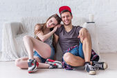 Friends girl and boy sitting on floor at home in summer jeanswear street urban casual style talking, having fun — Stock Photo