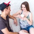 Friends girl with cup of coffee and guy sitting on sofa at home in summer jeanswear street urban casual style talking, having fun — Stock Photo #72992643