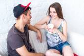 Friends girl with cup of coffee and guy sitting on sofa at home in summer jeanswear street urban casual style talking, having fun — Stock Photo