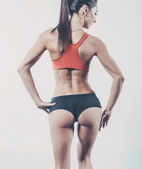 Muscular active athletic young woman with sexy buttocks posing showing muscles of the back shoulders and hands fitness, sport, training diet lifestyle concept. — Stock Photo