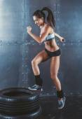 Sporty active fit woman box jumping. Female athlete is performing tire jumps fitness, sport, training and lifestyle concept. — Stock Photo
