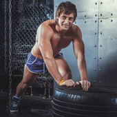 Sportswoman. Fit sporty man resting after exercising push ups on tire strength power training looking at camera concept crossfit fitness workout sport and lifestyle. — Stock Photo