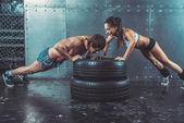 Sportswomen. Fit sporty woman and man doing push ups on tire strength power training concept crossfit fitness workout sport lifestyle. — Stock Photo
