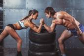Athlete muscular sportsmen man and woman with hands clasped arm wrestling challenge between a young couple Crossfit fitness sport training lifestyle bodybuilding concept. — Стоковое фото