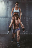 Athlete muscular sportsman doing exercising squats with woman sitting on his shoulders Crossfit fitness sport training lifestyle bodybuilding concept. — Стоковое фото