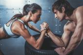 Athlete muscular sportsmen man and woman with hands clasped arm wrestling challenge between a young couple Crossfit fitness sport training lifestyle bodybuilding concept. — Stock Photo
