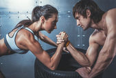 Athlete muscular sportsmen man and woman with hands clasped arm wrestling challenge between a young couple Crossfit fitness sport training lifestyle bodybuilding concept. — 图库照片