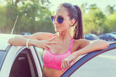 Attractive young fit woman wearing sunglasses standing by her car smilling showing v-sign, victory gesture or peace outdoors portrait. — Stock Photo