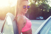 Athlete sporty fit young woman in sports bra wearing sunglasses standing leaning on car with door open looking at camera. — Stock Photo