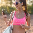 Athlete woman listening music looking at smartphone after workout in nature outdoors portrait summer evening on the beach holidays and vacation healthy lifestyle — Stock Photo #75202269