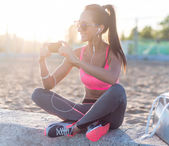 Athlete woman taking picture with smartphone camera, listining music, chatting on the beach summer holidays and vacation healthy lifestyle — Stock Photo
