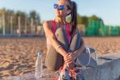 Beautiful fitness athlete woman wearing sunglasses listening music resting after work out exercising on summer evening in beach at sunset outdoor portrait. — Stock Photo