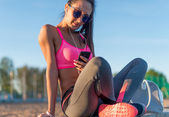 Beautiful fitness athlete woman wearing sunglasses resting listening music after work out exercising on summer evening in beach at sunset with smartphone outdoor portrait. — Stock Photo