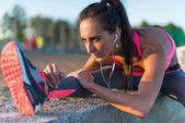 Kobieta lekkoatletycznego rozciąganie jej ścięgno, nogi ćwiczenia trening fitness przed treningiem poza na plaży w letni wieczór z słuchawki słuchać muzyki — Zdjęcie stockowe
