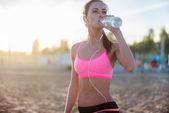 Vackra fitness idrottsman kvinna vila dricksvatten efter arbete ut utövar på stranden sommarkväll i soliga solskenet utomhus porträtt — Stockfoto