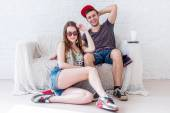 Friends smiling girl and boy at home in summer jeanswear street urban casual style talking, having fun. — Stock Photo