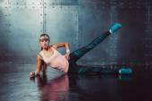 Athlete woman exercising warming up and stretching lying on her side the floor with  leg raised concept training fitness, sport, healthy lifestyle. — Photo