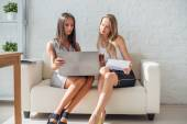 Two business woman friendly discussion during break in office using notebook and drinking coffee. — Stock Photo