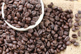 Coffee beans placed on bag sack and white cup. — Stock Photo
