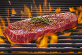 Flame Broiled Steak on a Hot Flaming BBQ Grill — Stock Photo