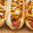 Постер, плакат: Three delicious chili hot dogs on a wood cutting board