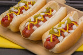 Three delicious hot dogs with mustard, ketchup, onions and pickle relish — Stock Photo