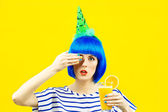 Girl in a blue wig holding a glass of orange juice on a yellow background — Stock Photo